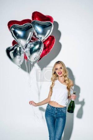 Photo pour La fille blonde gaie retenant des ballons et la bouteille de champagne sur le blanc - image libre de droit