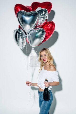 Photo for Happy blonde girl holding balloons and bottle of champagne while standing on white - Royalty Free Image