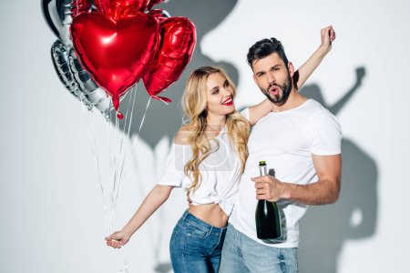 Photo for Cheerful woman holding balloons and looking at bearded man with bottle of champagne on white - Royalty Free Image