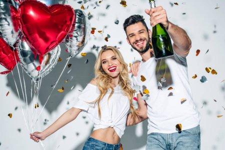 Foto de Enfoque selectivo de hombre alegre barbudo sosteniendo botella de champán cerca de la mujer con globos cerca de confeti en blanco - Imagen libre de derechos