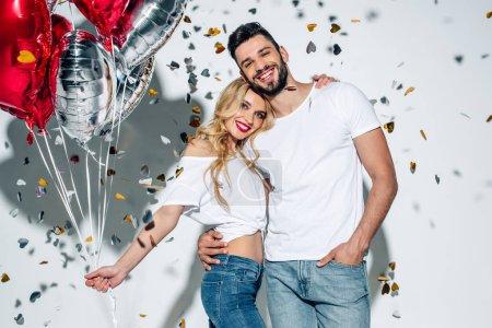Foto de Happy bearded man hugging cheerful blonde girl with balloons near confetti on white - Imagen libre de derechos
