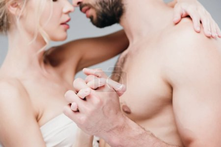 Photo for Cropped view of muscular shirtless man and blonde girl holding hands on grey - Royalty Free Image