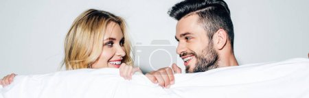 Photo for Panoramic shot of happy blonde woman and cheerful man looking at each other while holding blanket on white - Royalty Free Image