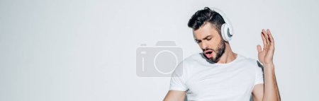 Photo pour Panoramic shot of handsome man listening music in headphones and singing on white - image libre de droit