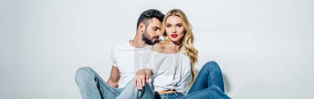 Photo for Panoramic shot of handsome bearded man sitting and looking at attractive blonde girl on white - Royalty Free Image