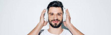 Photo pour Prise de vue panoramique de l'homme joyeux touchant écouteurs tout en écoutant de la musique et souriant sur blanc - image libre de droit