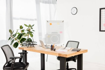 Photo for Modern office with white board, plant and laptop on desk - Royalty Free Image