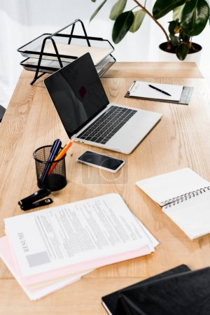 Photo for Modern office with smartphone, laptop, resume and blank notebook on desk - Royalty Free Image