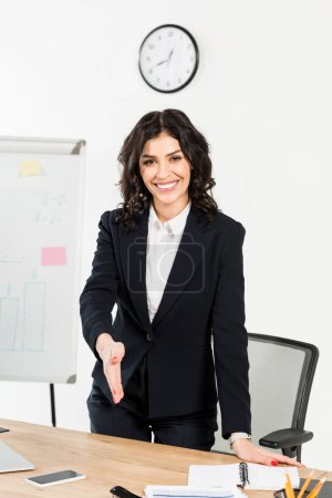 Photo for Cheerful brunette recruiter smiling while gesturing in office - Royalty Free Image