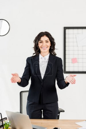 Photo for Happy brunette recruiter smiling while gesturing in office - Royalty Free Image