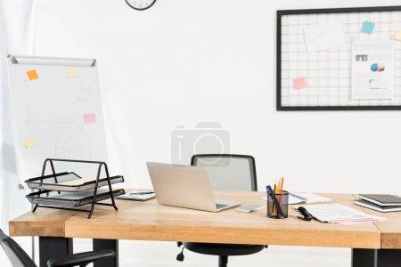 Foto de Oficina moderna con pizarra y portátil en escritorio de madera - Imagen libre de derechos