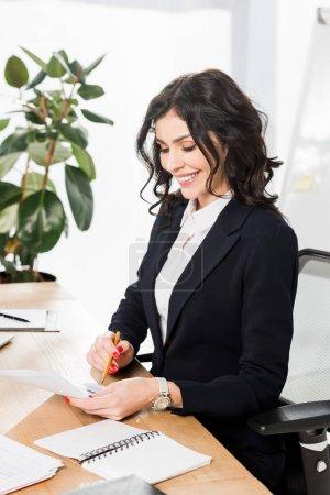 Photo pour Recruteur brun heureux dans l'usure formelle regardant le document et retenant le crayon dans le bureau - image libre de droit