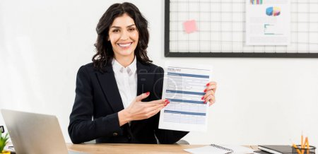panoramic shot of cheerful recruiter holding resume and gesturing in office