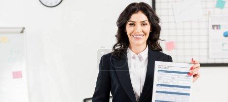 Photo pour Tir panoramique de recruteur gai tenant CV dans le bureau - image libre de droit