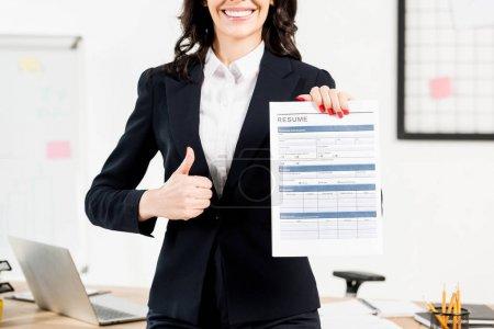 Photo pour Vue recadrée de recruteur de brunette gai retenant le résumé et affichant le pouce vers le haut - image libre de droit
