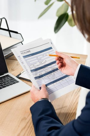 Photo for Selective focus of man holding resume and pencil near laptop - Royalty Free Image