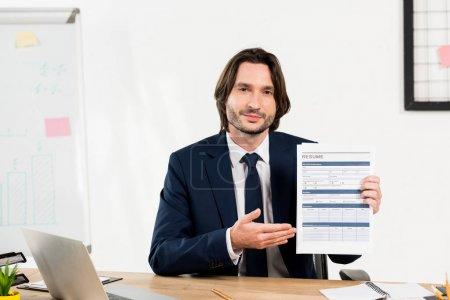 Photo pour Beau recruteur gesticulant tout en tenant CV dans le bureau - image libre de droit