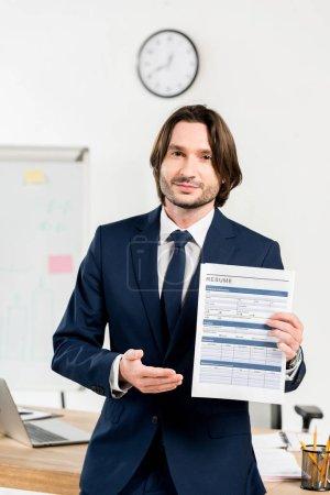 Photo pour Bel homme dans l'usure formelle tenue CV et gesticulant dans le bureau - image libre de droit