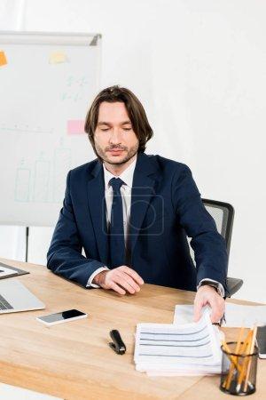 Photo pour Beau recruteur de prendre des curriculum vitae tout en étant assis dans le bureau - image libre de droit