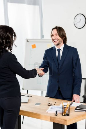 Photo pour Handsome recruiter shaking hands with brunette woman in office - image libre de droit