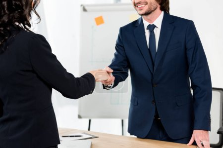 Photo for Cropped view of happy recruiter shaking hands with brunette woman in office - Royalty Free Image
