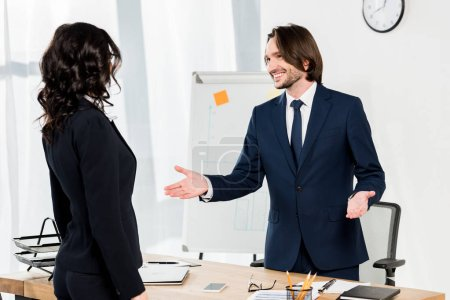 Photo for Handsome recruiter gesturing near brunette woman in office - Royalty Free Image