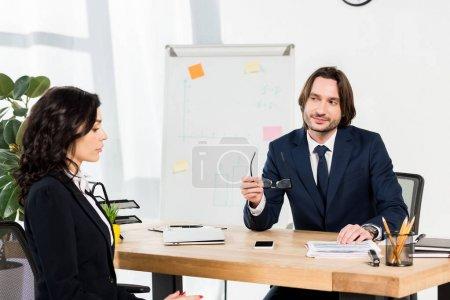 Photo pour Beau recruteur retenant des glaces et regardant la femme attirante dans le bureau - image libre de droit