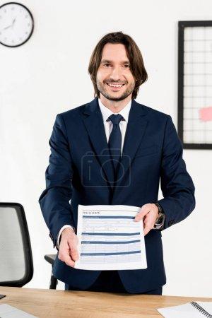 Photo pour Beau recruteur souriant tout en tenant le résumé dans les mains - image libre de droit
