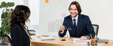 Photo pour Panoramic shot of happy recruiter holding glasses and looking at brunette woman in office - image libre de droit