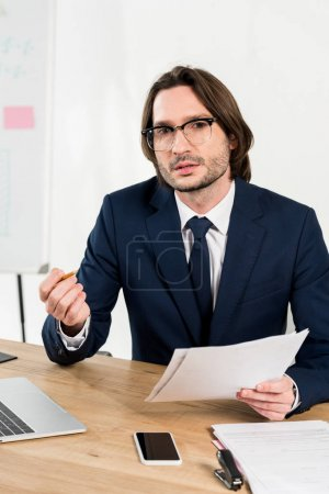 handsome man in glasses holding documents and looking at camera