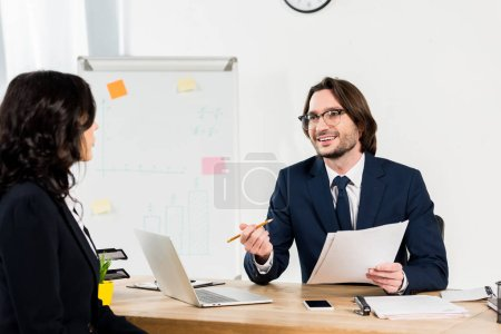Photo for Selective focus of happy recruiter in glasses holding documents and looking at woman - Royalty Free Image