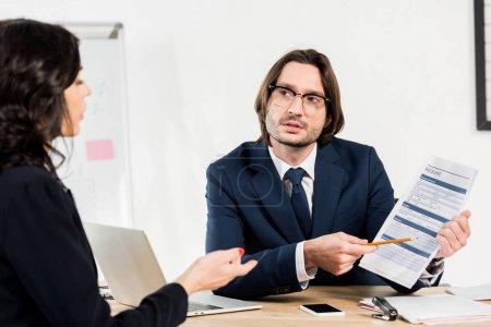Photo pour Foyer sélectif du recruteur dans les verres retenant le résumé près de la femme - image libre de droit