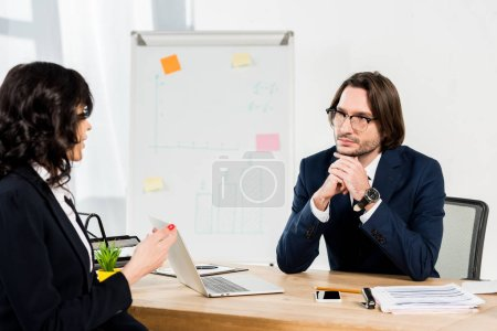Photo for Selective focus of recruiter in glasses looking at woman in office - Royalty Free Image