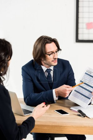 Photo pour Focus sélectif du recruteur dans les lunettes regardant le résumé et faisant des gestes près de la femme - image libre de droit