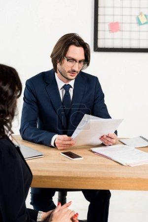 Photo pour Recruteur sélectif de bel foyer dans des glaces regardant des documents près de la femme se tenant avec les mains serrées - image libre de droit