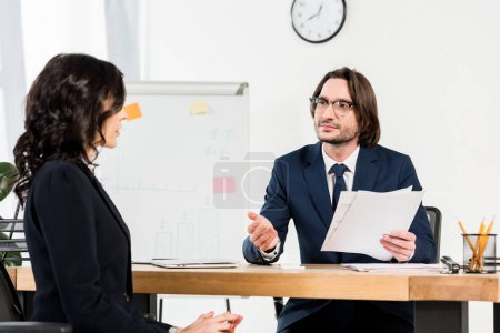 Photo pour Selective focus handsome recruiter in glasses holding documents and gesturing near beautiful woman - image libre de droit