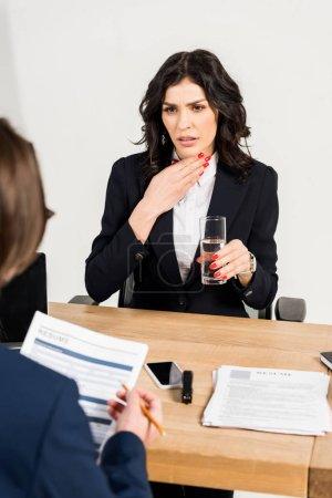 Photo pour Foyer sélectif de la femme attirante retenant le verre de l'eau près du recruteur - image libre de droit