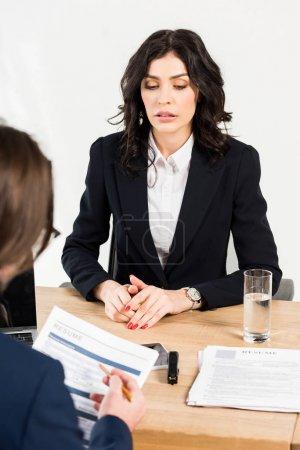 Photo pour Foyer sélectif de la femme attirante s'asseyant près du recruteur avec le résumé - image libre de droit