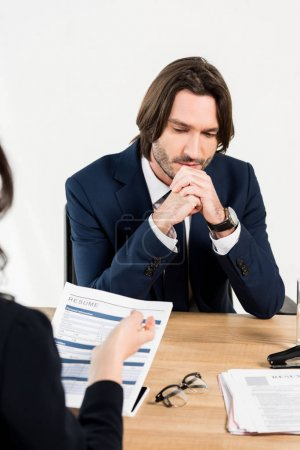 Photo for Selective focus of worried man sitting with clenched hands near recruiter - Royalty Free Image