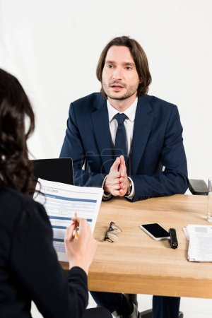 Photo for Selective focus of handsome man talking while having job interview in office - Royalty Free Image