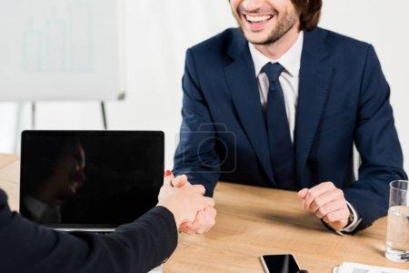 Photo pour Vue recadrée de l'homme gai se serrant la main avec le recruteur dans le bureau - image libre de droit