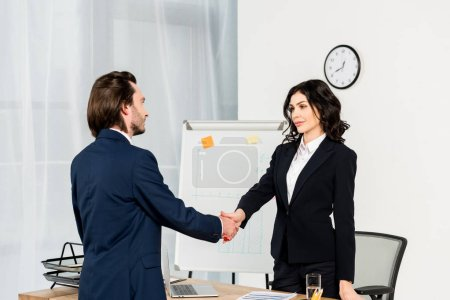 Photo for Attractive recruiter shaking hands with handsome employee in office - Royalty Free Image