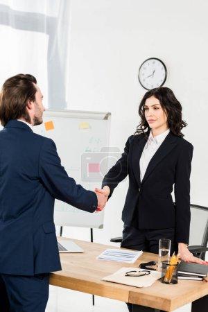 Photo pour Recruteur de brunette attrayant serrant la main avec l'employé dans le bureau - image libre de droit