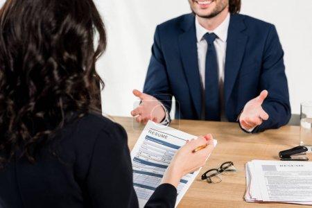 Photo pour Orientation sélective de CV dans les mains du recruteur près de l'homme en fonction - image libre de droit