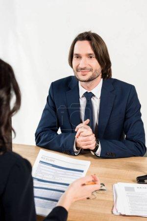 Photo pour Foyer sélectif de l'homme souriant avec les mains serrées regardant le recruteur avec le résumé - image libre de droit