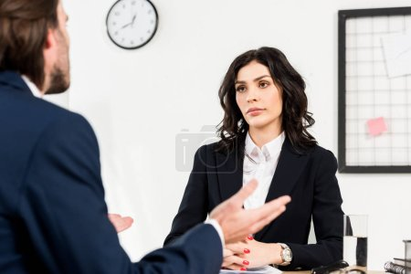 Photo for Selective focus of attractive recruiter looking at man gesturing during job interview - Royalty Free Image