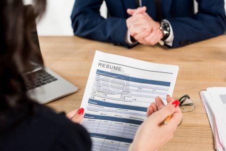 Photo pour Vue recadrée de recruteur tenant le résumé près de l'employé avec les mains serrées - image libre de droit