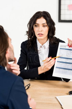 Photo pour Selective focus of attractive recruiter holding resume near man during job interview - image libre de droit