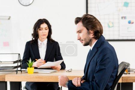 Photo pour Foyer sélectif de l'homme beau s'asseyant près du recruteur attrayant dans le bureau - image libre de droit