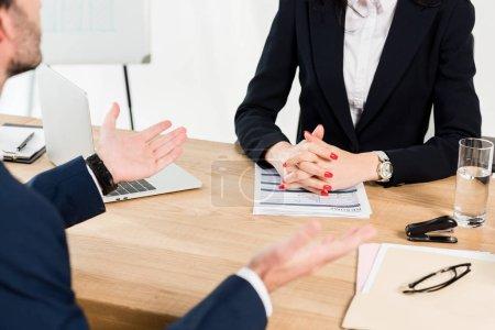 Photo pour Vue recadrée du recruteur s'asseyant avec les mains serrées près de l'homme faisant des gestes dans le bureau - image libre de droit